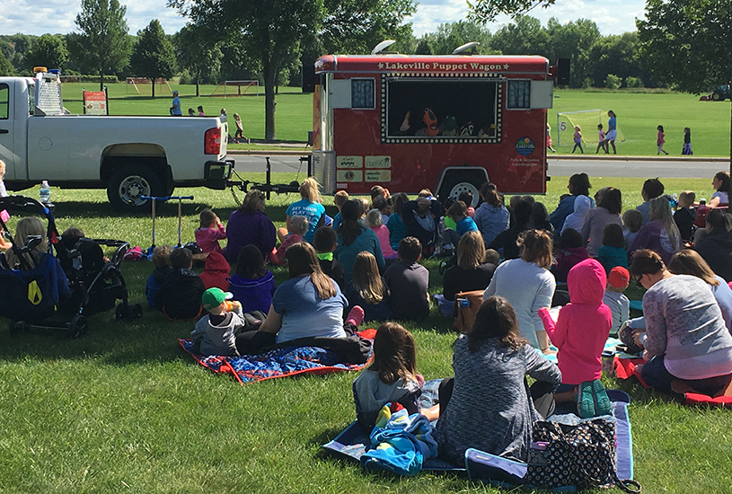 kids watching a puppet show outdoors at a park