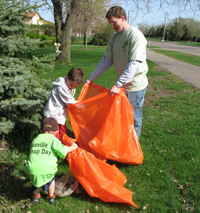 dad and kids picking up litter